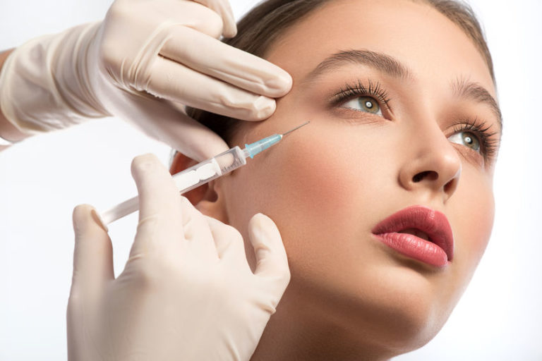 a woman receiving a treatment of Botox on her eye area to treat wrinkles